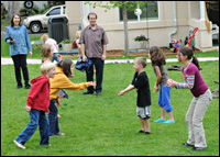 A bunch of chlidren playing, as two adults look on